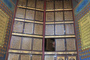 A wall made up of carved wooden panels showing pages of the Qur'an at a boarding school in the city of Palembang, Indonesia.