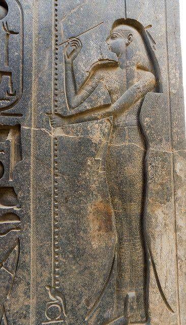 """Representación de Seshat, """"Señora de los libros"""", diosa de la escritura y la historia; medidora del tiempo; fundadora de templos y protectora de sus bibliotecas.  Ésta  representación  la podemos encontrar en la estatua sedente de Ramsés II en el templo de Luxor. Data de alrededor del 1250 a.C y la muestra escribiendo y describiendo los años futuros del reinado del faraón."""