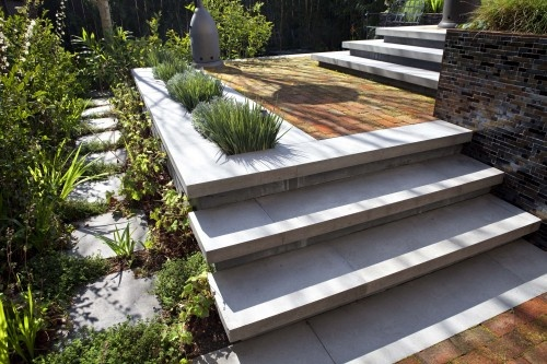 combination of new concrete, reclaimed brick, and plantings.