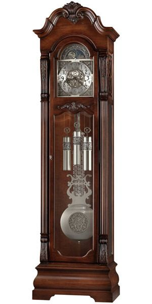 "Howard Miller Neilson 611-102 Grandfather Clock   The distinctive bonnet pediment of this floor clock finished in Embassy Cherry features a dramatic carved shell framed by stepped swan neck pediment moldings. Astrological blue moon phase. The dial includes a silver chapter ring with applied satin black finished Arabic numerals.   Cable-driven, Westminster chime Kieninger movement with automatic nighttime chime shut-off option.  Size: H. 84-1/4"" W. 23"" D. 13-3/4"""