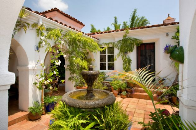 Small infomal Spanish style courtyard entrance to a house with white walls and red tile roof.