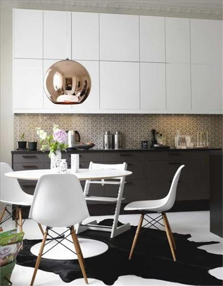 Black & white modern kitchen with mid century chairs. Two colours uppers and lowers. Brass round globe pendant lighting. Animal hide rug.