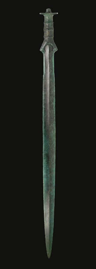 A EUROPEAN BRONZE SWORD SOUTH-CENTRAL EUROPE, BRONZE AGE, CIRCA 12TH-10TH CENTURY B.C. The lanceolate blade inserted into the separately-cast hilt, the blade with a peaked midrib, the edges serrated toward the hilt, lentoid in section, the baluster-shaped grip with three raised bands, incised with dotted scrolling and hatching along the length, the edges riveted on either side, the knobbed pommel incised with concentric circles and dots on the exterior, rows of dots on the underside…