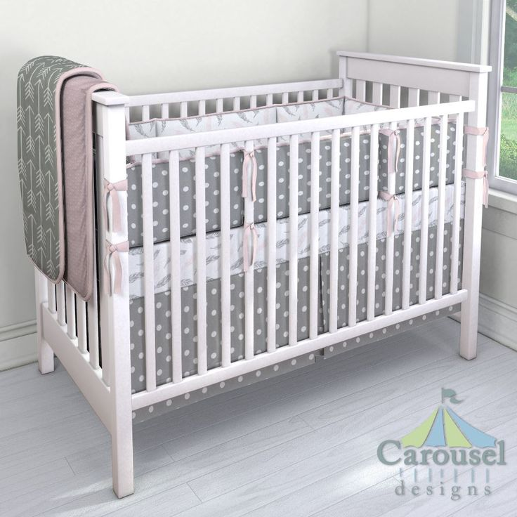 Crib bedding in Blush Pink and Silver Gray Hand Drawn Feathers, Gray and White Polka Dot, Solid Pink, Pink Dimpled Minky, Gray Arrow. Created using the Nursery Designer® by Carousel Designs where you mix and match from hundreds of fabrics to create your own unique baby bedding. #carouseldesigns