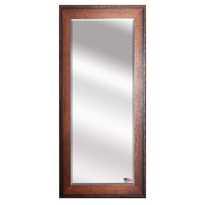 This understated full-length timber estate Wall Mirror demonstrates a classic American craftsman style. Outlining the beveled mirror, the frame features a simple sturdy look with a pleasant warm walnut finish that appears slightly aged. The rivet trim accent adds the charming character that will complement your traditional style.