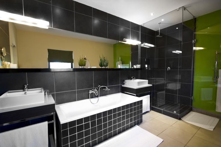 Luxury Bathroom - Green: These suites have large floor to ceiling windows overlooking the rolling landscape of the Klipriviersberg; they are located in the bush area of Thaba Ya Batswana ensuring quiet privacy. Each air-conditioned suite is equipped with large screen LCD television, and iPod docking station.