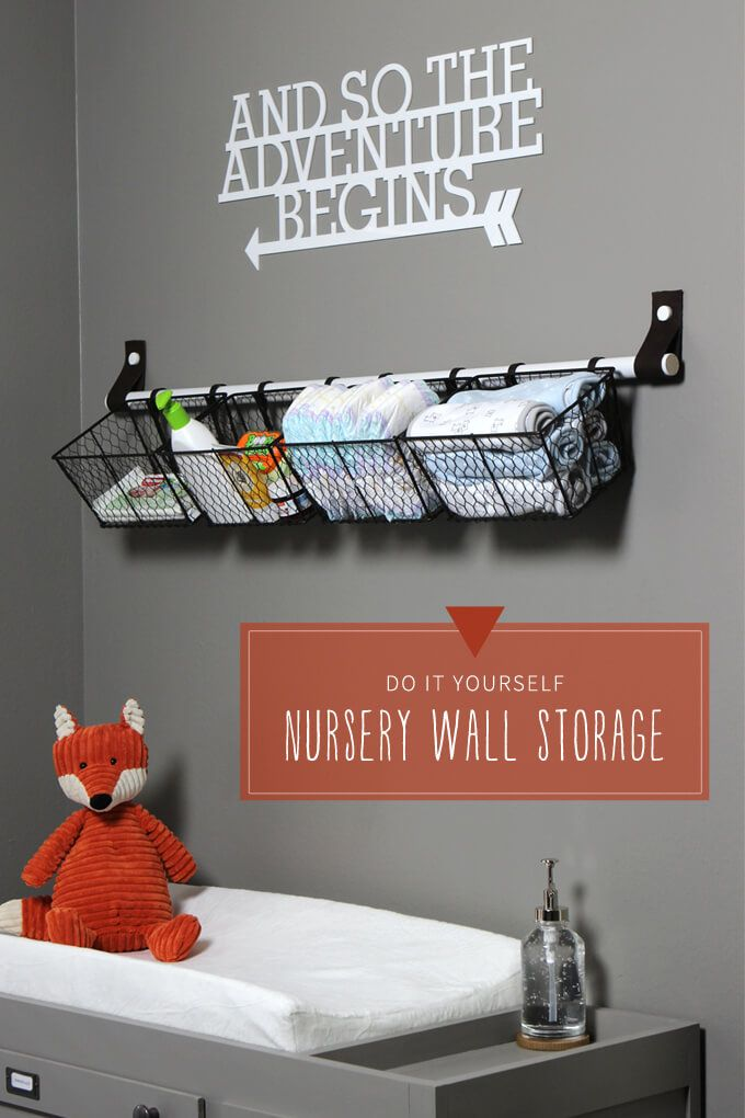 Nursery wall storage solution for above baby changing table made from a dowel rod and leather straps. Baskets make it easy to store diapers and baby supplies so they are easy to grab.