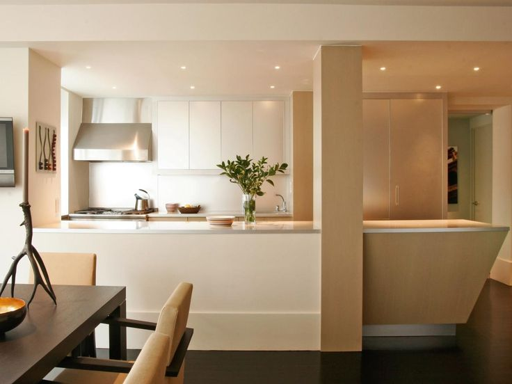 Blonde wood accents add subtle contrast to this kitchens white palette and visually define the hall