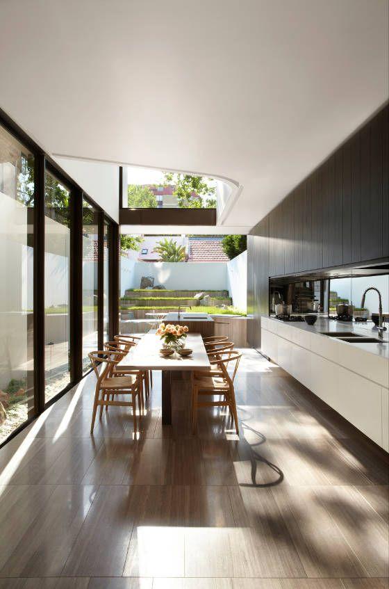 Cuisine épurée blanche et meubles hauts en alcôve en bois brun. Belle ligne des meubles bas, crédence miroir et grande baie vitrée.