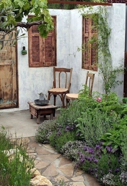 Wooden shutters, wooden furniture and a wooden door help transform this patio into a cozy, outdoor space that feels like home.
