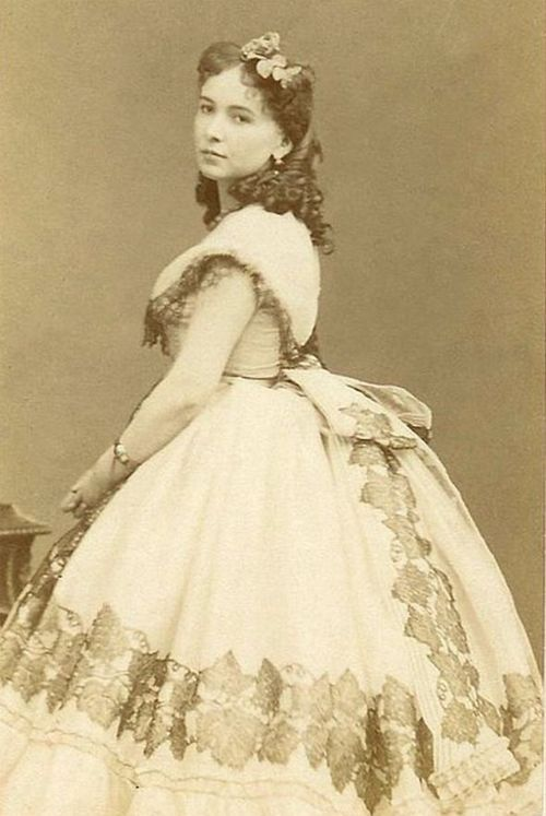 "Striking French beauty (and famed courtesan) Cora Pearl. [Assuming she is at the forefront of fashion, this dates probably from 1864, or possibly late 1863 or early 1865. The ""horned"" hairstyle, slightly raised straight waist, and tiny sleeves are brand new. The skirt is still very full, however, and doesn't really show the new ellipitical shape.]"