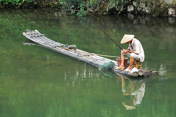 In early August of 2006, I found this fisherman at the edge of a tributary that feeds the Lijiang. I was in Guilin, in one of the most picturesque areas of China. This is the traditional raft that fishermen have used on the Lijiang for centuries, plying the shallower waters of the river with their pole, and otherwise riding the persistent current to their next destination. #fisherman, #China, #Guilin