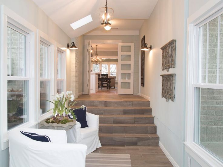 The new breezeway takes full advantage of the large windows on both walls, allowing light to fill the area. Lighter, more natural flooring and a calming paint color make the space large and airy. Two chairs create a beautiful place for Carolyn or guests to relax and read.