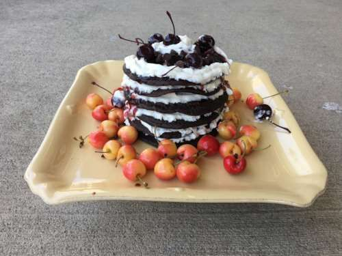 Chocolate pancakes are layered with cherry puree and whipped cream in this clever black forest pancake cake, a twist on the classic dessert. HELLO BREAKFAST.