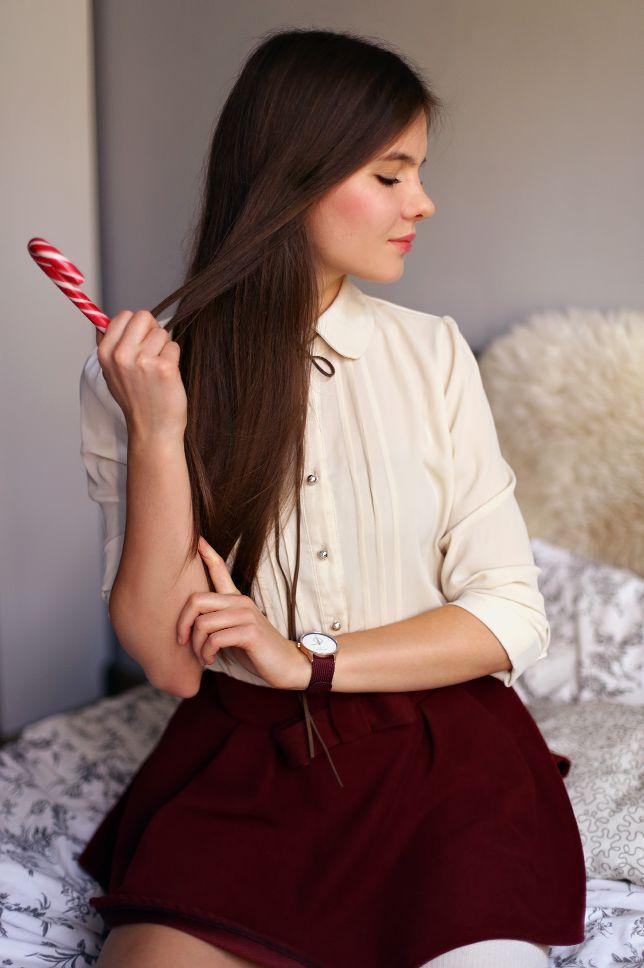 Beżowa koszula, bordowa spódniczka, kremowe zakolanówki i zegarek na czerwonym pasku