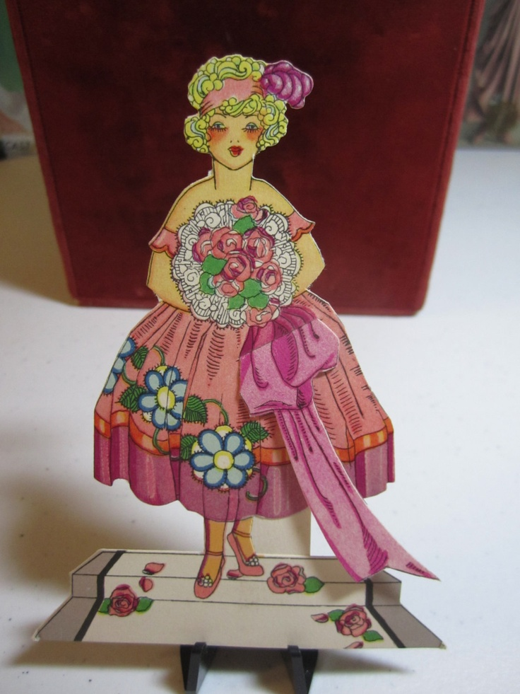 Gorgeous unused 1920's colorful die cut place card and bridge tally of a flapper holding a flower bouquet wearing ballerina shoes slippers.  via Etsy.