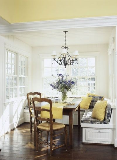 White wood nook seating with dark wood table and chairs. Mellow yellow. <3  Should recover my chairs in patterned fabric in same shade of yellow as my walls.