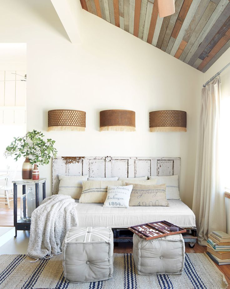Planks from Habitat for Humanity's ReStore line the sitting-room ceiling in this renovated Texas cottage. The homeowner was inspired to turn cow-feed sifters found at the Round Top Antiques Fair into artful sconces with burlap fringe.   - CountryLiving.com