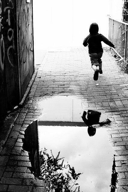 Henri Cartier-Bresson. In this photo I like how the reflection in the puddle is so clear, the water is like glass. I also like how you can not see past the person. It is bright so gives you an image in your head and seems weird.