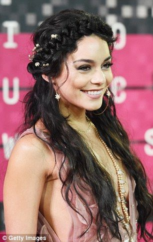 Raven-haired beauty: Her long dark hair was styled in rippling waves, partially braided an...