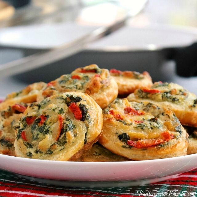 Spinach Dip Pinwheels - Everyone's favorite dip gets even better when it's combined with puff pastry. Spinach dip pinwheels studded with roasted red peppers are the ultimate holiday appetizer and one that is always a hit! | ButtercreamBlondie.com