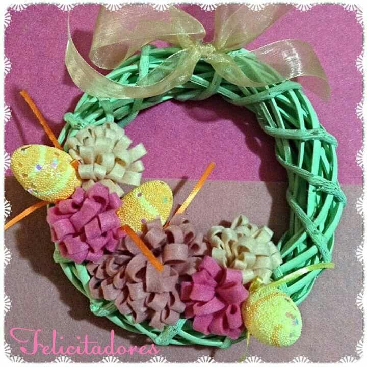 Ghirlanda pasquale con decorazioni floreali realizzate in feltro...