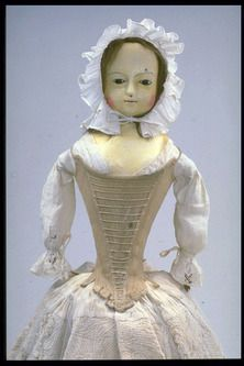 Wooden doll with painted face, human hair and glass eyes. Doll is wearing a lace trimmed linen chemise, two petticoat (one is quilted linen,...