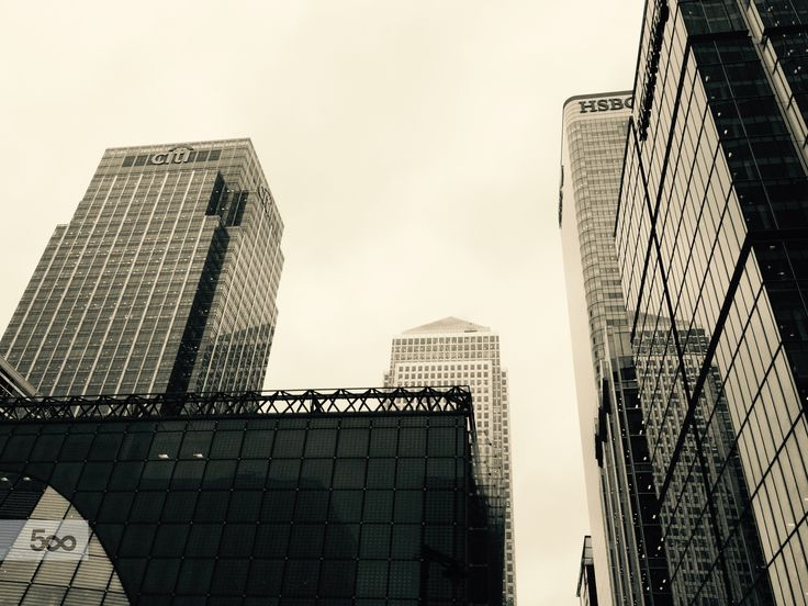 The buildings at canary wharf standing up high like giants made out of steel.