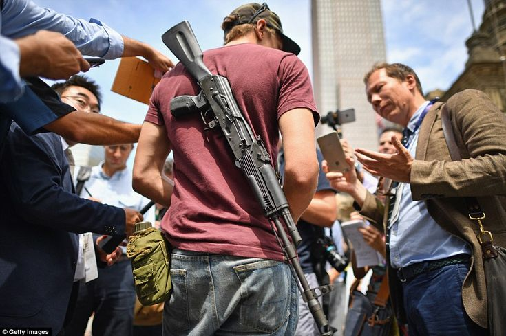 Jessey Rodriguez stands with his AK-101- rifle on his back outside the Republican National...
