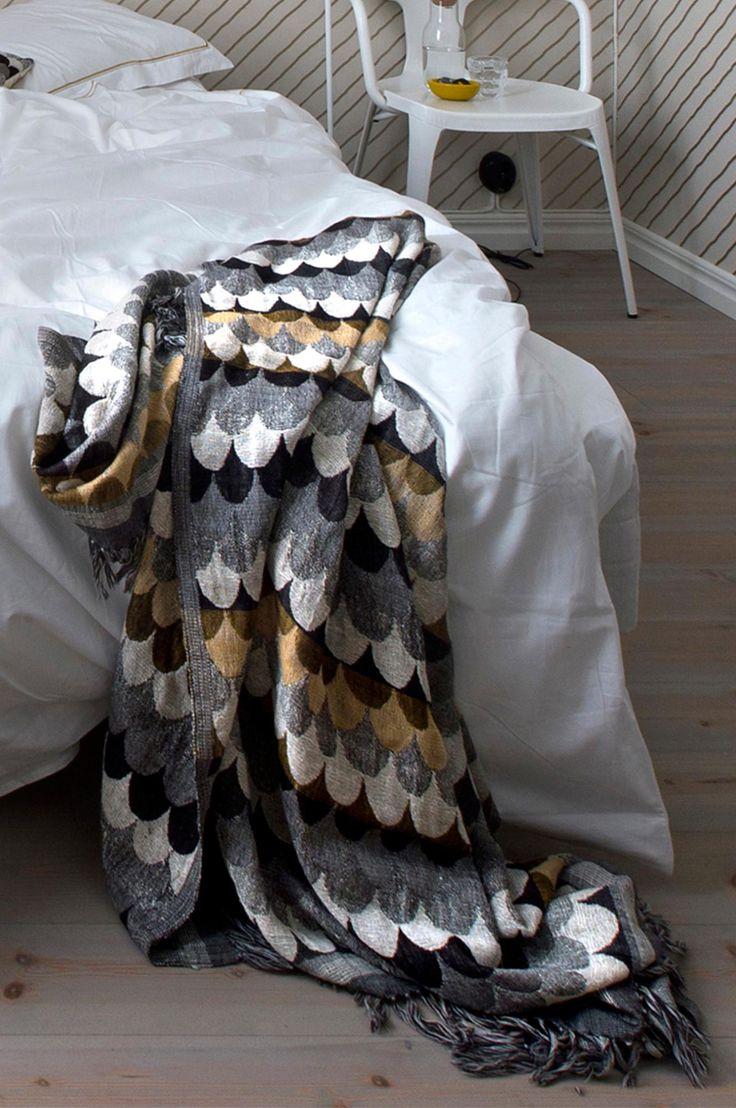 Dekorativt pledd som er vevd for hånd av håndspunnede tråder i silke og ull. Det vakre mønsteret skifter i svart, grått, kremhvitt og oker og finnes også som pute. 60% ull 40% siden. 30 ° skånsom maskinvask i ullprogram, renses eller forsiktig håndvask i kaldt vann. Størrelse 130x170 cm