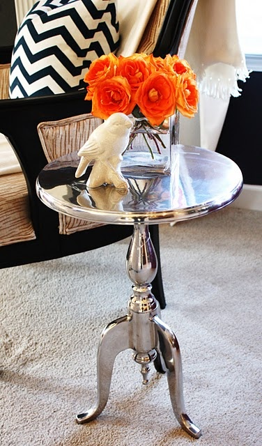 Glossy silver painted side table, orange flowers and black and white chevron printed pillow