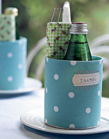 A lata revestida de tecido indica o lugar, acomoda o guardanapo, os talheres e ainda uma garrafinha de água