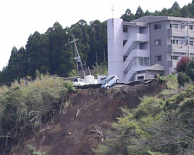 地震の影響で駐車場が崩れ、落ちそうな車=熊…:熊本県で震度7の地震 写真特集:時事ドットコム