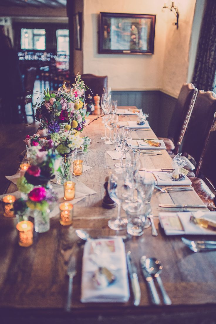 Quirky pub top table with glass jars filled with bright flowers | A winter wedding | Enzoani Fada lace wedding dress, | bright colour scheme | pink bridesmaid dresses | Rustic decor | Vintage Inspiration | Photography by Hayley Baxter | http://www.rockmywedding.co.uk/steph-paul/