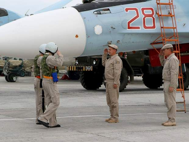 Russian servicemen salute as air force pilots arrive to board a Russian Sukhoi Su-30SM fighter jet before departure on a mission at the Russian Hmeimin military base