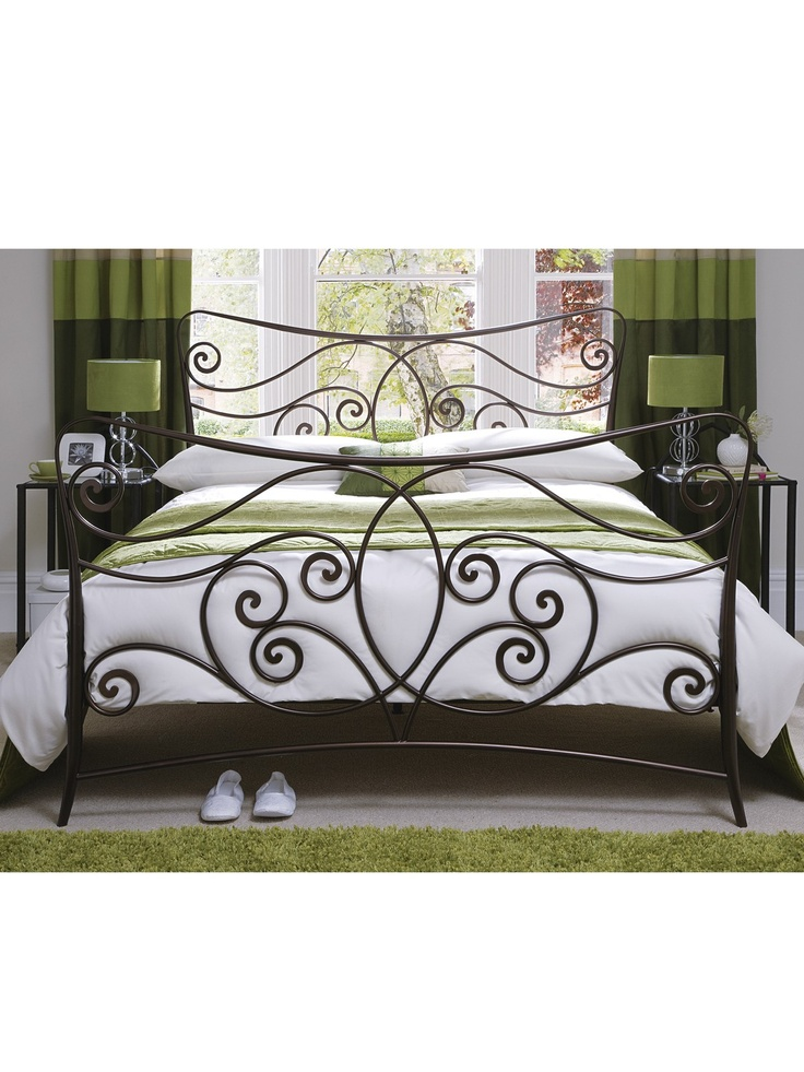 green bedroom with metal bed