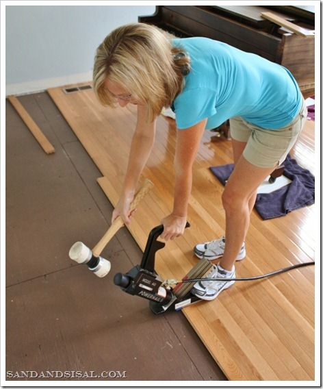 That's Kim of Sand and Sisal using a pneumatic nail gun (rented from The Home Depot!) to install hardwood flooring. She has a full how-to on her blog, with handy tips and videos to show how she installed the flooring. || @sandandsisal
