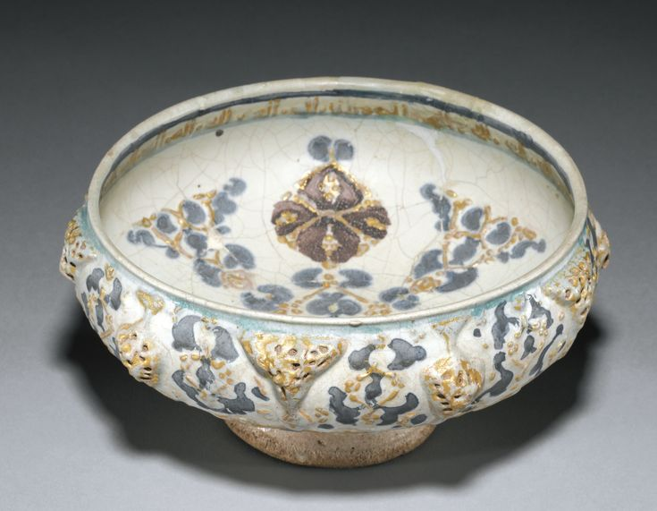 A FINE KASHAN MINAI POTTERY BOWL, PERSIA, 13TH CENTURY of deep rounded form on a short hollow foot and with a slightly inverted rim, decorated in turquoise, blue and manganese with relief beige motifs and gilt highlights, the well with a central stylised foliate design and calligraphic band under the rim, the exterior with ensuite design and pierced geometric bosses in high relief
