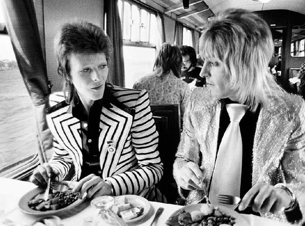 David Bowie & Mick Ronson are having a perfect English breakfast on a train, in 1973. Pic found on www.mrbreakfast.com