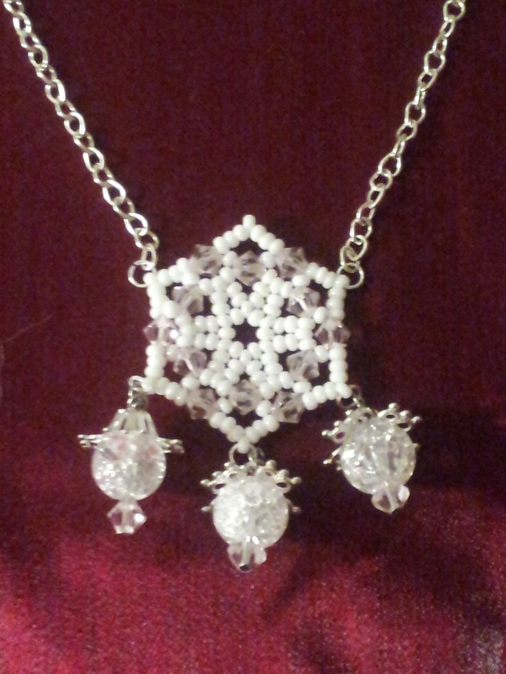 A solitary snowflake with Swarovski crystal accents and crackle bead dangles.