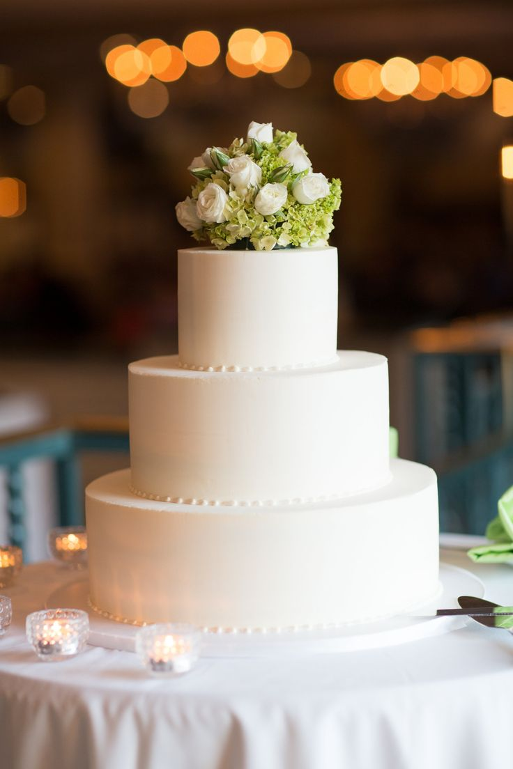 Simple white wedding cake. White butter cream wedding cake. Lime green floral topper.