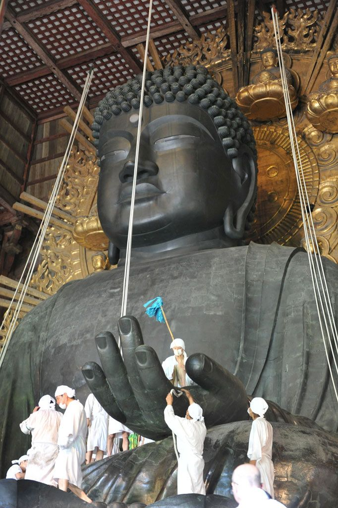 Cleaning Japan's biggest Buddha in Todai-ji Temple, Nara, Japan