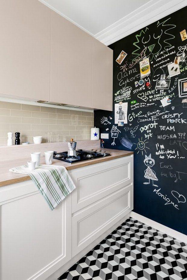 """Jedna ze ścian w kuchni została pomalowana farba tablicową. Miały być na niej zapisywane """"rzeczy do zrobienia"""", ale na razie jest zapełniona wpisami przyjaciół. Żeby nie było nudno, szafki dolne i górne mają różne fronty."""