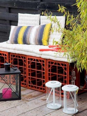 Si buscas decorar tu patio con ideas originales, junta cuatro cajas y ponlas encima de un cojín largo junto a otros cojines de diferentes diseños y colores.