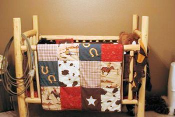 Rustic homemade pine log baby crib for a log cabin or western cowboy baby nursery with patchwork baby quilt bedding.