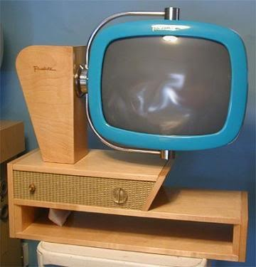 .turquoise tv attached to blonde wood table