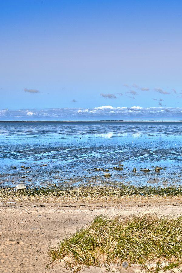 De Waddenzee is een uniek natuurgebied dat niet voor niets op de Unesco werelderfgoedlijst staat. De binnenzee strekt zich uit over een lengte van 500 kilometer en ligt in drie verschillende landen: Nederland, Duitsland en Denemarken. Deze foto toont het wad gezien vanaf het Duitse Waddeneiland Amrum, tussen de dorpen Norddorf en Nebel. Aan de horizon zien we niet het vasteland maar een ander eiland, Föhr, dat midden in de Waddenzee ligt.