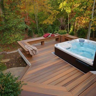 This curved deck is tucked into the woods for lots of privacy. It feature a main deck area and a lower deck dedicated for the hot tub. Skirting is around the main deck and here Fiberon composite decking is used run vertical.