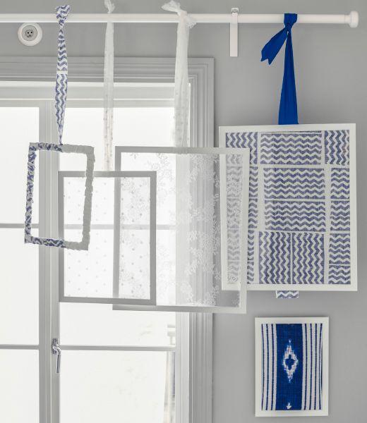 Biele rámy s textíliami vo vnútri zavesené na závesovej tyči.