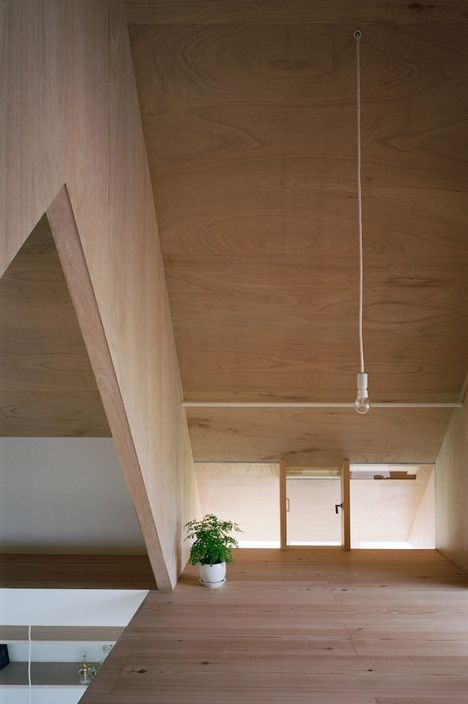 Small attic spaces are tucked between the ribs of a triangular roof at this house extension in Japan